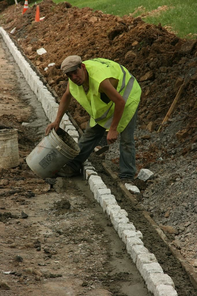A Man Putting Cement In Between Stone Road Barriers