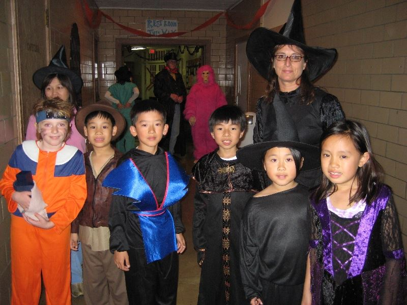Group of Children and an Adult in Halloween Costumes