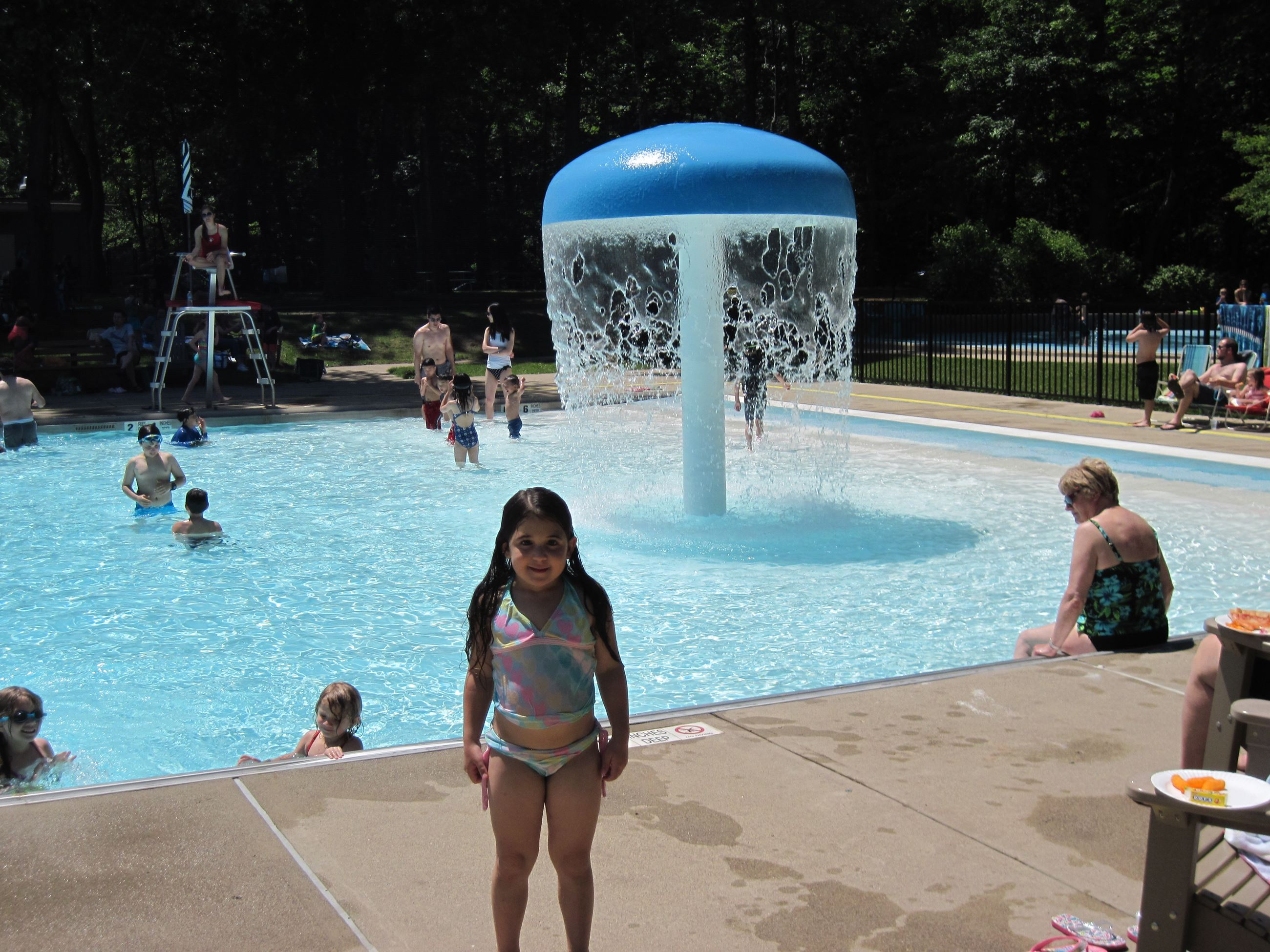 Little Girl Standing in Front of a Pool