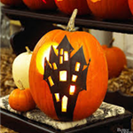 Photo of a pumpkin with a haunted house silhouette on it with light shining through the window cutou