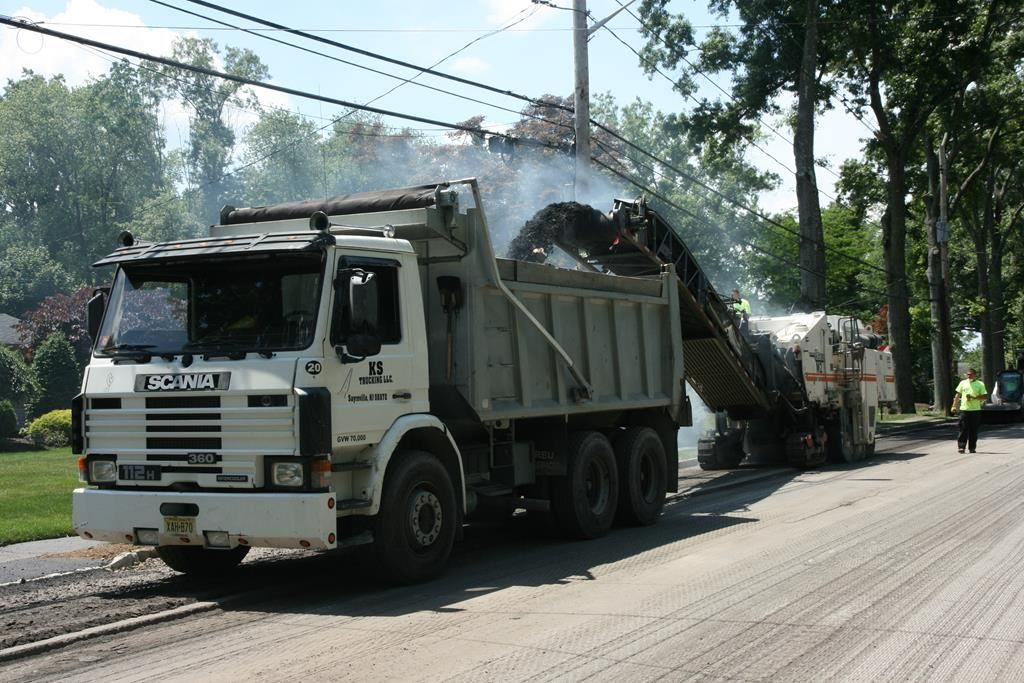 Machine Putting Torn Up Road into a Dump Truck