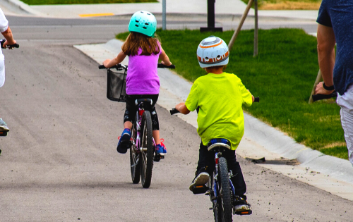 Two kids riding bikes down the street and wearing helmets