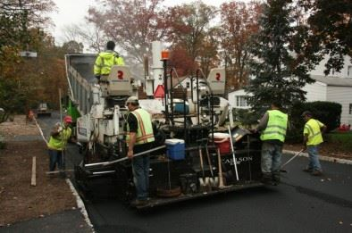 Workers re-paving a road.