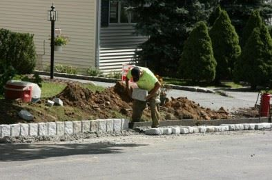 A man installing a stone barrier on the side of a road.