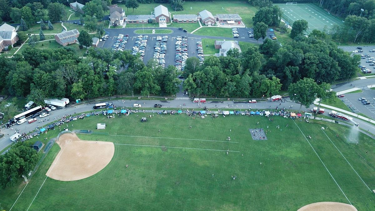 Aerial photo of side of the Oval showing tents, attendees, and vehicles