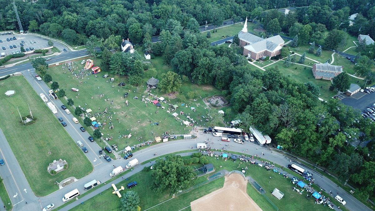 Aerial photo of corner of the Oval showing tents, attendees, vehicles, and small plane