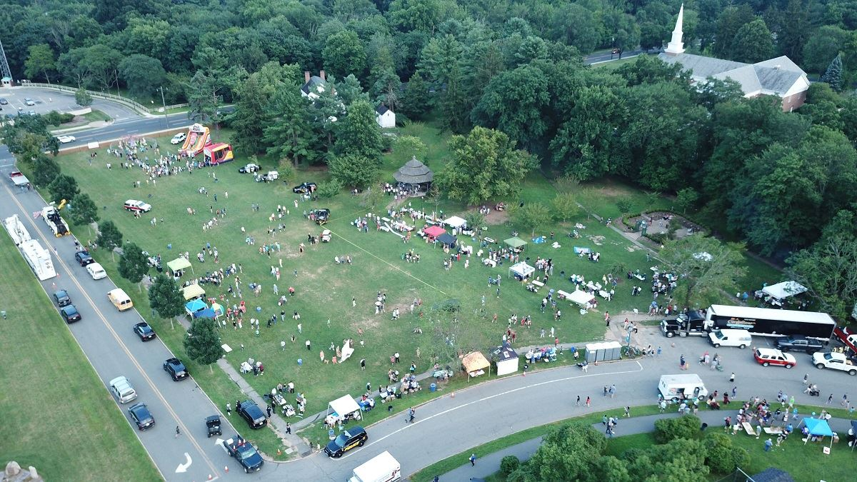 Aerial photo of grass between Oval & Livingston Ave. with bounce houses, tents, and people