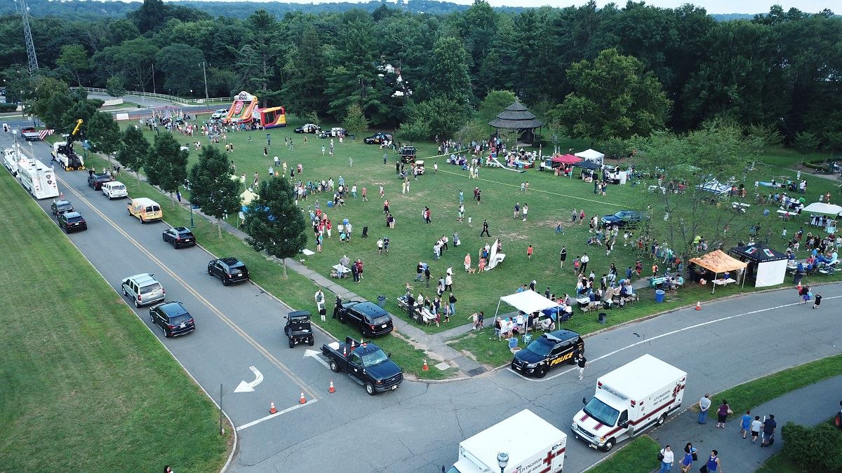 Drone photo of people, police vehicles, ambulances, and bounce houses at the Oval