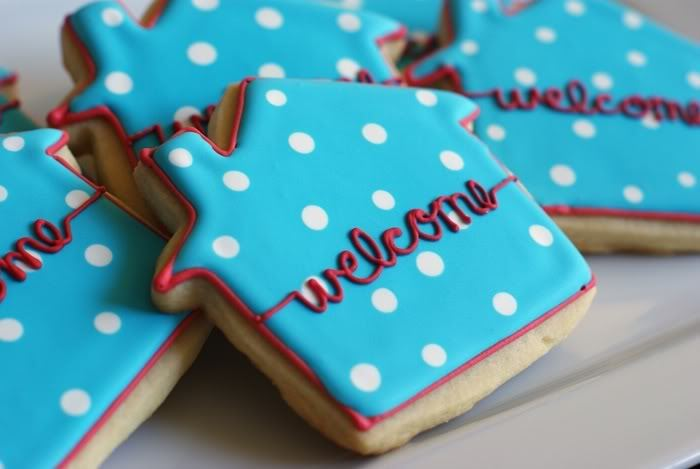 "Blue house-shaped cookies with white polka dots and ""welcome"" written in red"