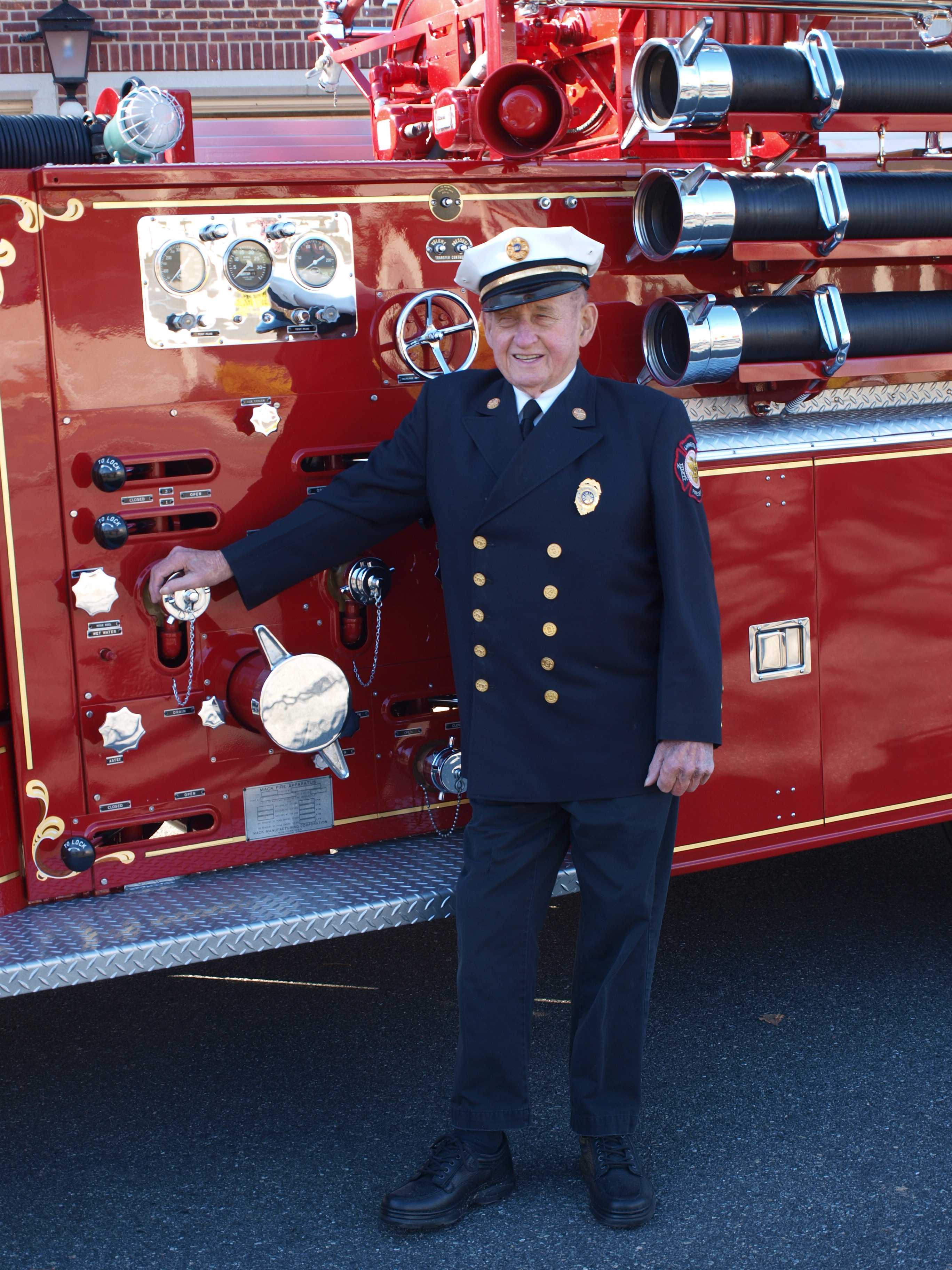 Chief Charlie Schilling dressed in uniform, with LFD Fire Truck