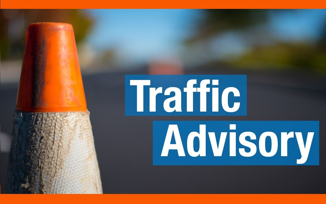 Close up of orange traffic cone with &#34Traffic Advisory&#34 in white text, highlighted in blue.