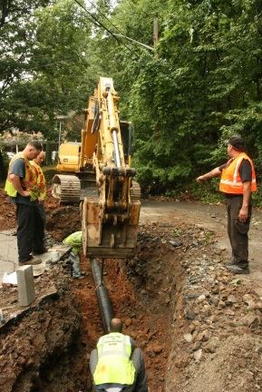 Excavator digging at site of water main