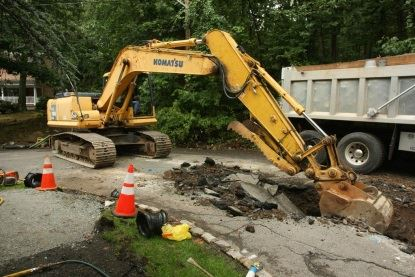 Excavator digging at site of water main (side view)